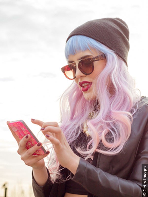 Woman with long unicorn hair, sunglasses and hat taps on her smartphone