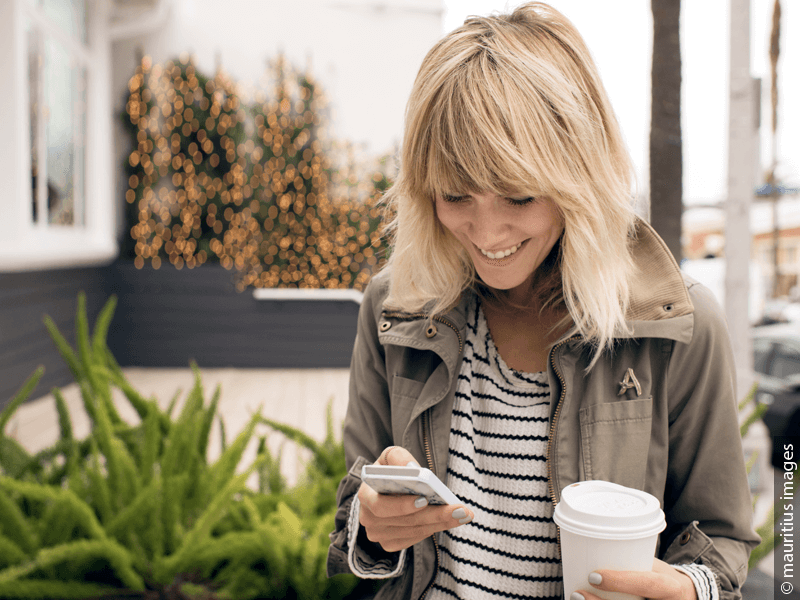 Blond woman with modern zigzag part holding a coffee cup and a smartphone
