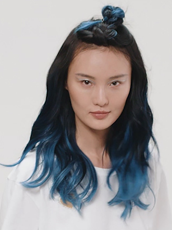 Woman with half bun and hair ends dyed blue.