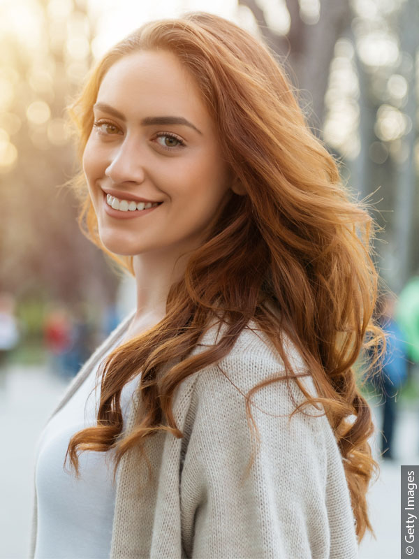 Redheaded woman with long hair in park