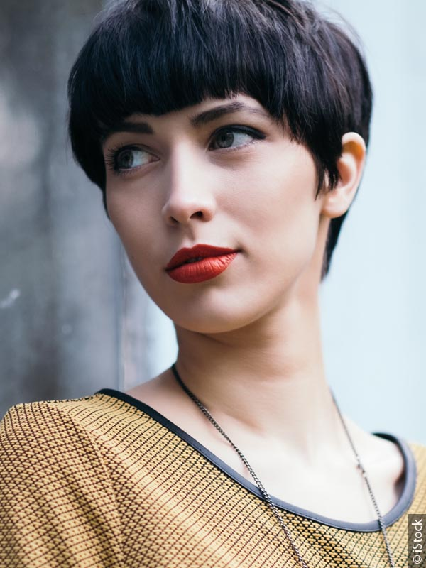 Woman with black hair cut into a sharp short style with bangs, wearing red lipstick and a mustard-colored shirt