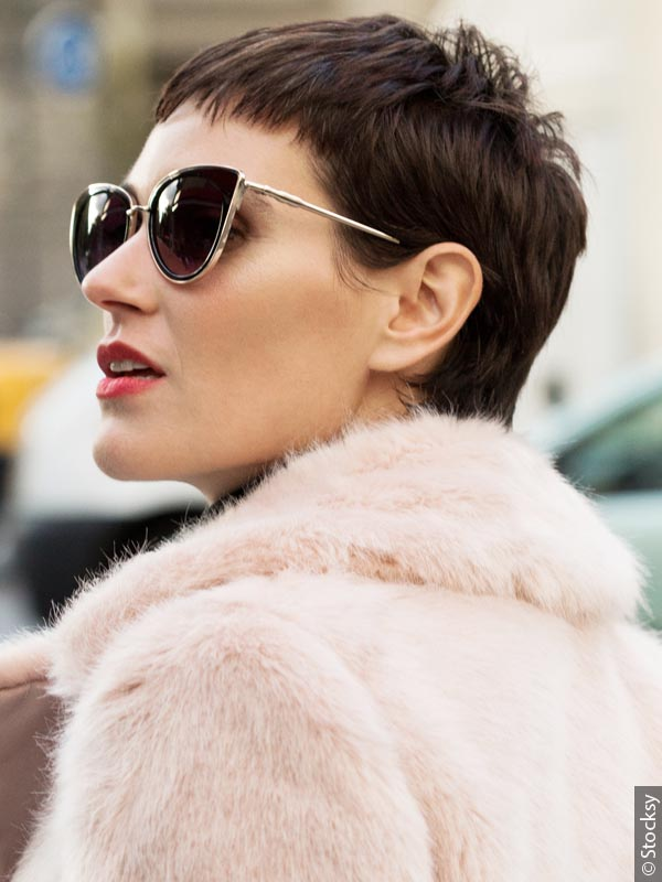 Sideview of a woman with a brunette pixie cut, wearing sunglasses and a pink fur coat