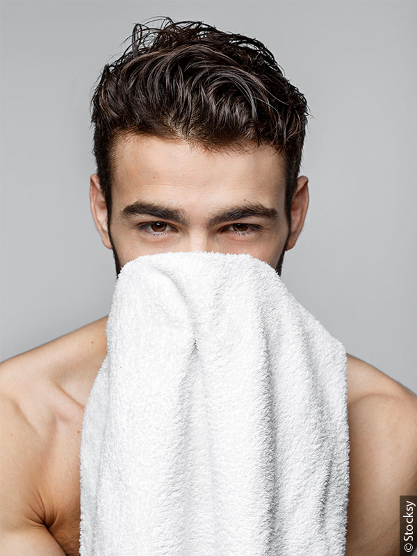 Man with full, dark brown hair holding a towel up to his face