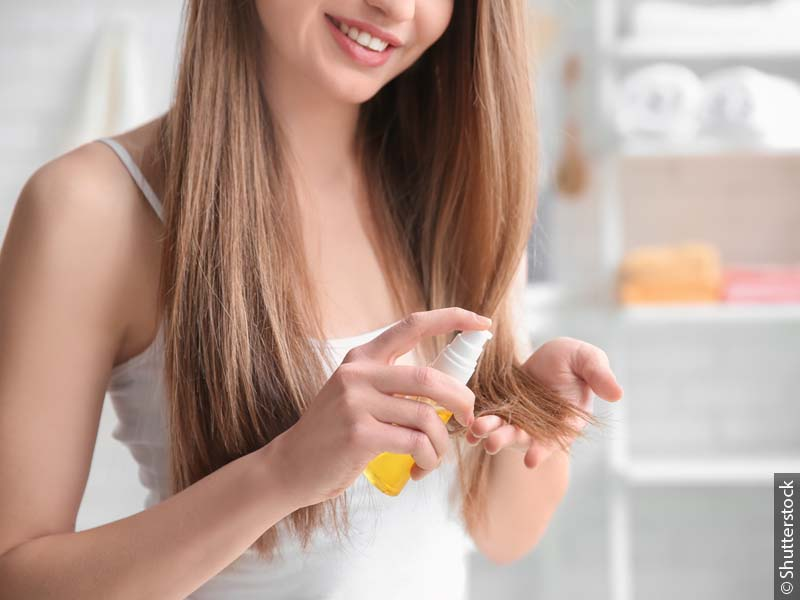 Woman with long blond hair applying tip treatment product