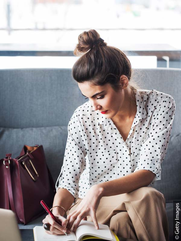 Brunette woman with a bun wearing business attire and writing notes