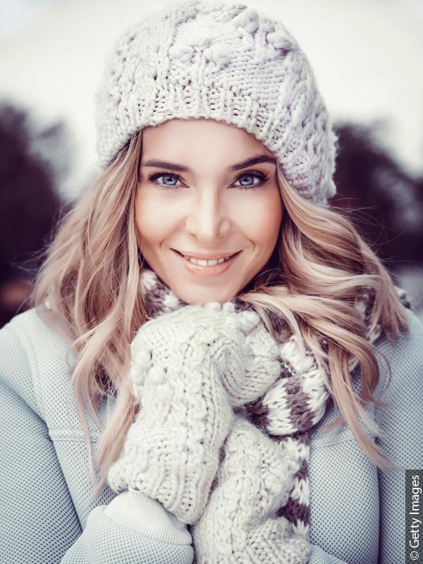 Young woman with long blond hair looking straight into the camera, wearing a light gray coat, knitted hat and matching mittens.