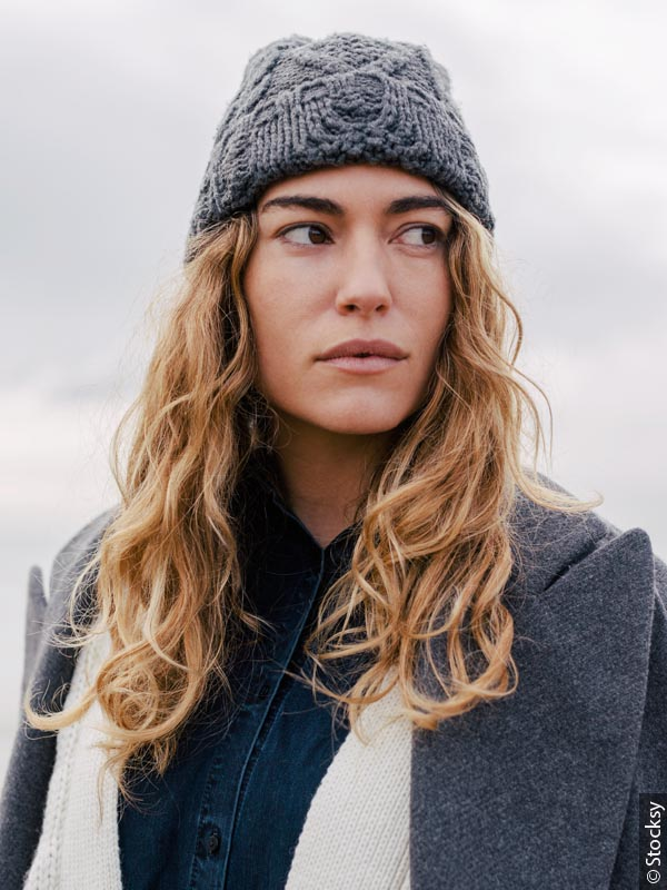 Young woman with long, dark blond, curly hair looks sideways. She wears a dark grey knit hat and a coordinating coat.