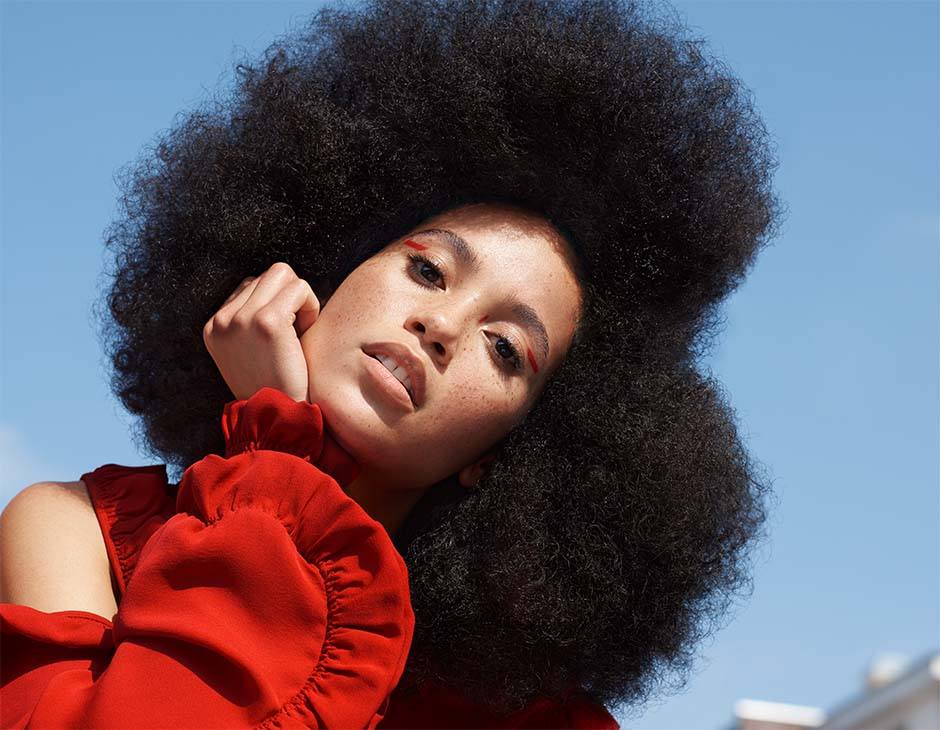 Woman wearing an afro styled in a new curls look.