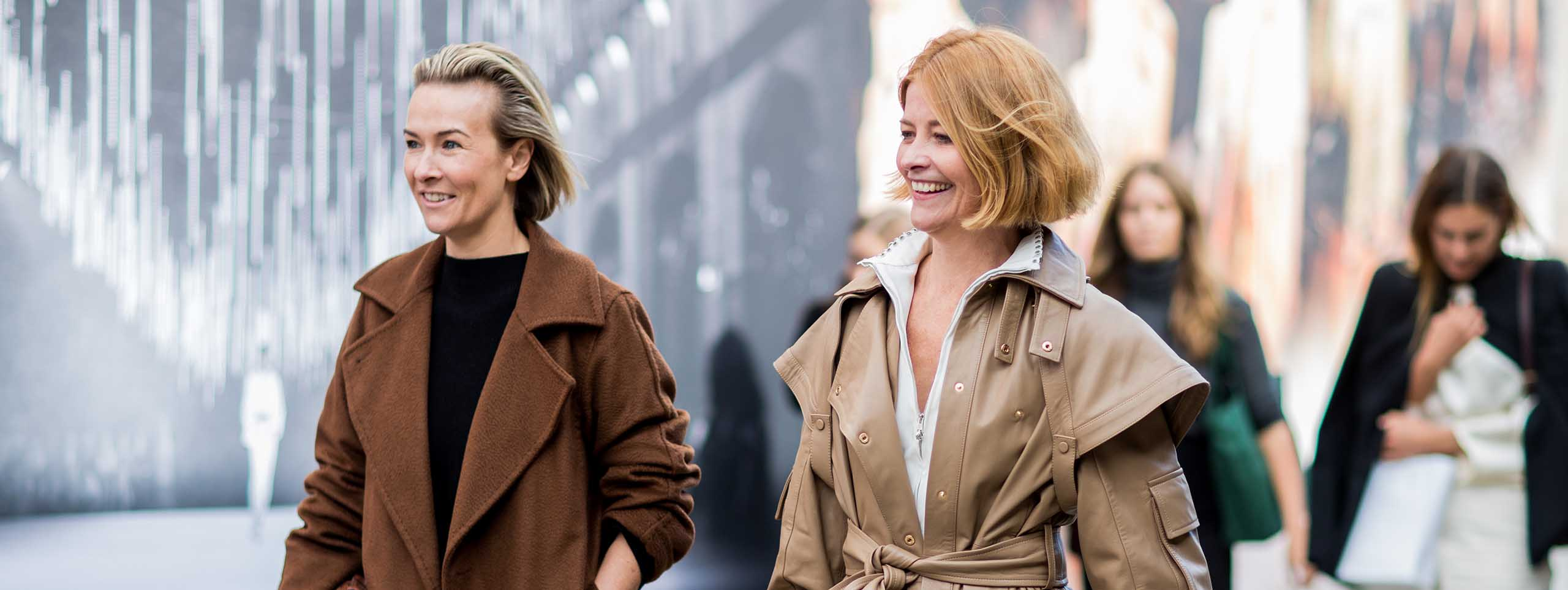 Two smiling older women with trendy hairstyles and coats
