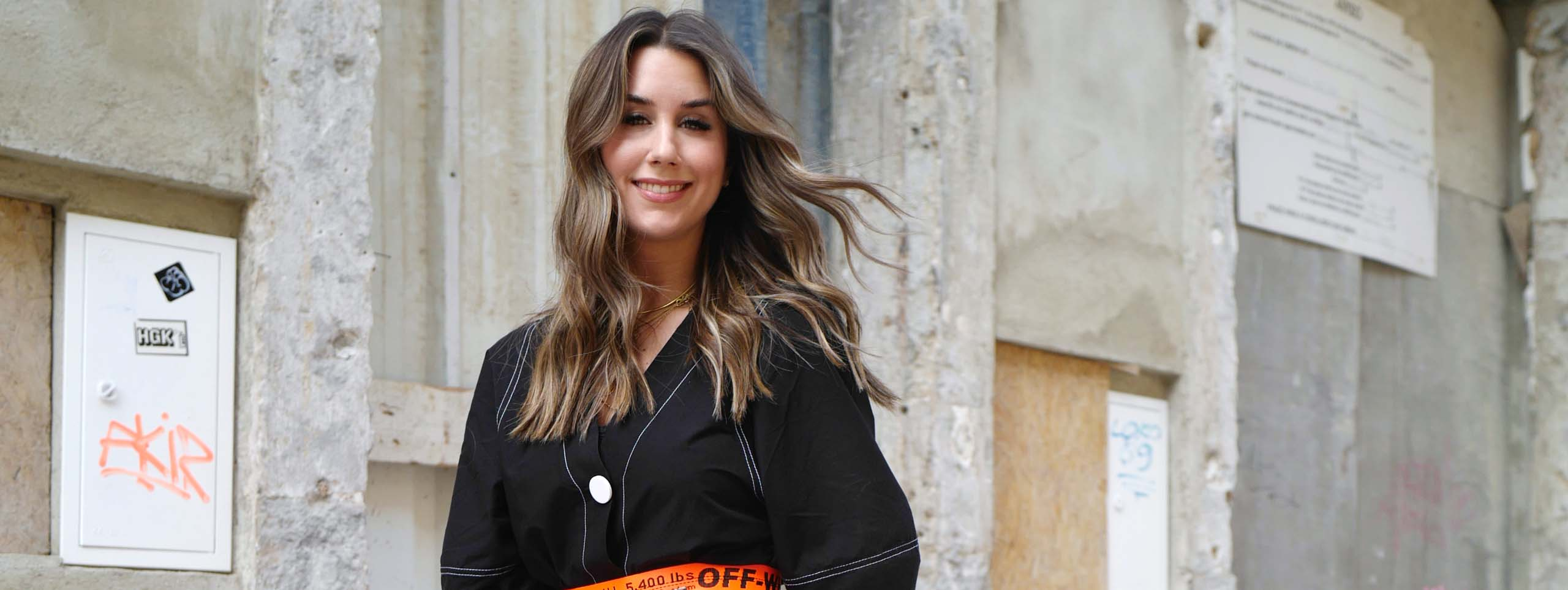 Blogger Janina Pfau with blond-highlighted, brunette beach waves blowing gently in the breeze