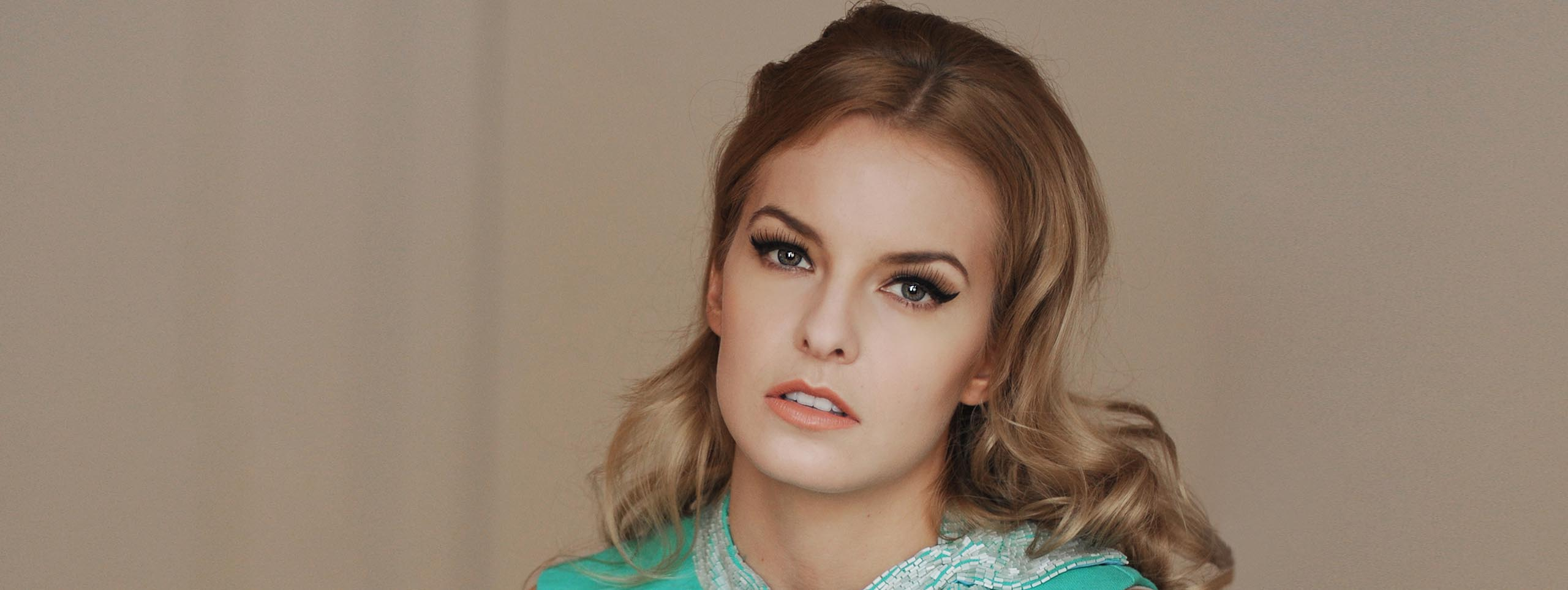 Woman with dark blond hair in half-up hairstyle, wearing a turquoise top and sixties style make-up.