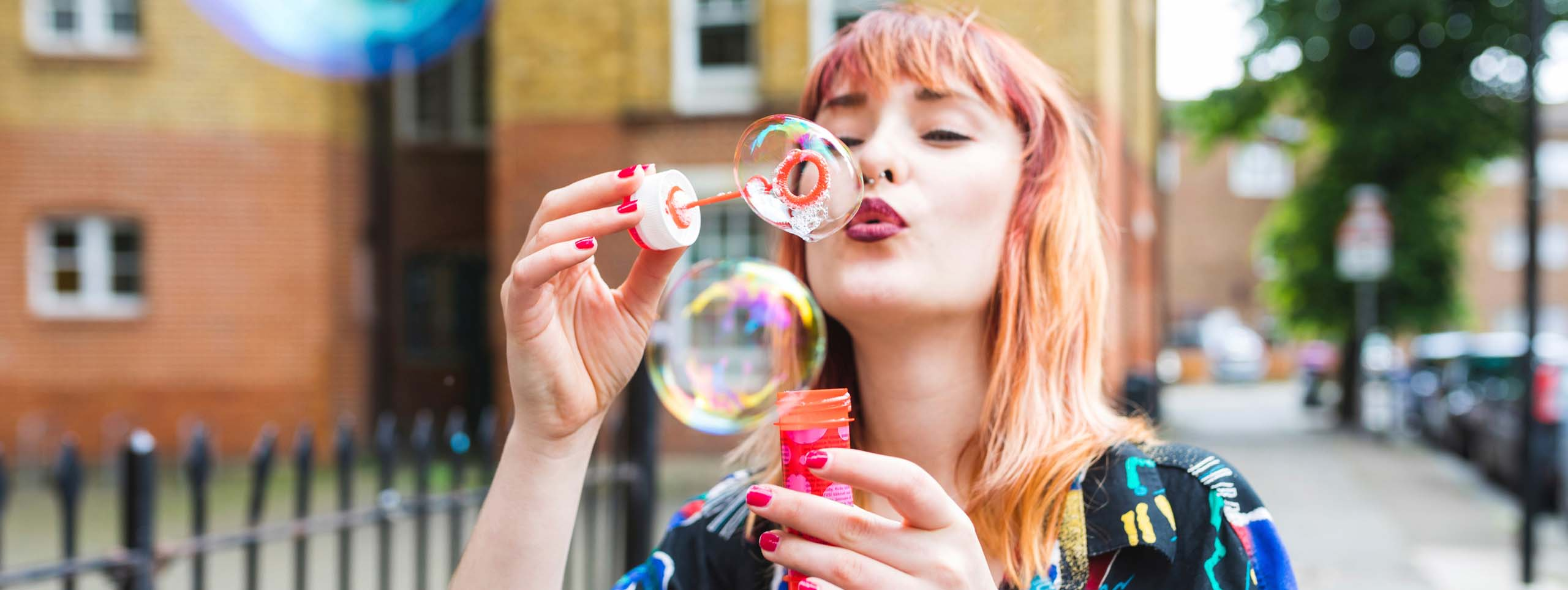 Young woman with unicorn hair blowing bubbles